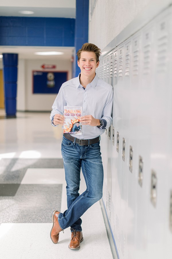 Noah - student at MCHS posing with his book
